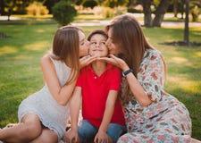 Gelukkige moeder, zoon en dochter in het park Het mamma en de zuster kussen hun zoon Gelukkig familieconcept royalty-vrije stock foto