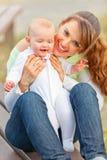 Gelukkige moederholding die aanbiddelijk babymeisje glimlacht Royalty-vrije Stock Afbeelding
