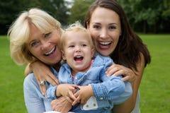 Gelukkige moederkleindochter en baby die in openlucht glimlachen Stock Afbeeldingen