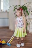 Gelukkige mooi weinig blond meisjes schoonmakend huis royalty-vrije stock foto's
