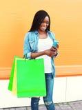 Gelukkige mooie Afrikaanse vrouw met het winkelen zakken die smartphone in stad gebruiken Stock Fotografie