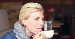 Gelukkige mooie blonde het drinken koffie stock videobeelden