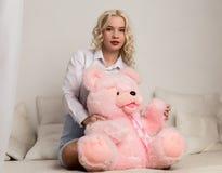 Gelukkige mooie blondevrouw die een teddybeer koesteren Concept vakantie of verjaardag stock foto's
