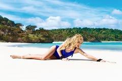 Gelukkige mooie blondevrouw met lang haar in een blauw zwempak o stock foto's
