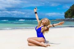 Gelukkige mooie blondevrouw met lang haar in een blauw zwempak o stock afbeelding