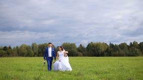 Gelukkige mooie bruid en bruidegom die op gebied lopen stock videobeelden