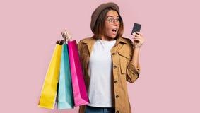 Gelukkige mooie donkerbruine vrouw na het winkelen en besteden veel geld van de echtgenoot` s creditcard, glimlacht zij stock fotografie