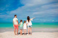 Gelukkige mooie familie op het strand Achtermening van ouders en jonge geitjes op de Caraïben Royalty-vrije Stock Afbeeldingen
