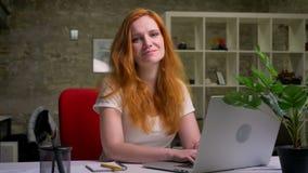 Gelukkige mooie glimlach die van Kaukasisch gembermeisje, bij haar Desktop zitten en laptop met behulp van tijdens arbeid, die ze stock footage