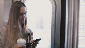 Gelukkige mooie glimlachende onderneemster in een metro die smartphone winkelen app gebruiken die zich bij het venster van de ing stock videobeelden