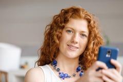 Gelukkige mooie jonge onderneemster die het slimme telefoon glimlachen gebruiken Royalty-vrije Stock Foto