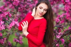 Gelukkige mooie jonge vrouw in bloesempark met bomen en bloemen Stock Foto's