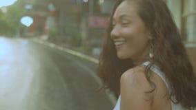 Gelukkige mooie jonge vrouw die langs de natte weg lopen stock footage