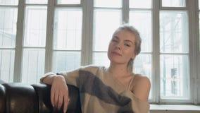 Gelukkige mooie jonge vrouw die terwijl het bekijken de camera lachen Een blonde glimlacht thuis tegen het venster stock video