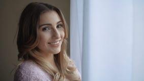 Gelukkige mooie jonge vrouw die uit het venster kijken stock footage