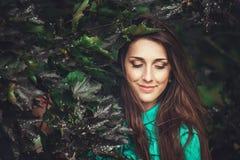 Gelukkige mooie jonge vrouw in het park van de de lentebloesem stock fotografie