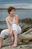 Gelukkige mooie jonge vrouw op een rotsachtig strand Royalty-vrije Stock Foto