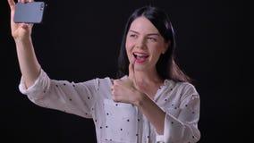 Gelukkige mooie jonge vrouw selfie en glimlachen die, die vredesteken tonen in camera nemen, op zwarte achtergrond wordt geïsolee stock footage