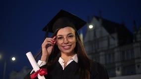 Gelukkige mooie jonge vrouwelijke gediplomeerde die aan camera glimlachen stock videobeelden