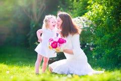 Gelukkige mooie moeder en haar dochter in tuin Stock Fotografie