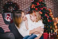 Gelukkige mooie moeder en haar weinig dochter het stellen dichtbij Kerstboom in een vakantiebinnenland Stock Foto