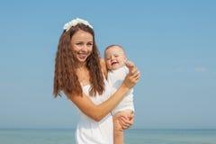 Gelukkige mooie moeder en zoon die strand van tijd genieten Stock Foto's