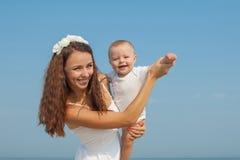 Gelukkige mooie moeder en zoon die strand van tijd genieten Royalty-vrije Stock Afbeeldingen
