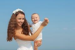 Gelukkige mooie moeder en zoon die strand van tijd genieten Stock Afbeeldingen