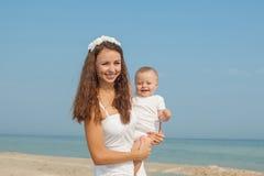 Gelukkige mooie moeder en zoon die strand van tijd genieten Stock Foto