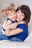 Gelukkige mooie moeder met een dochter thuis Royalty-vrije Stock Afbeelding