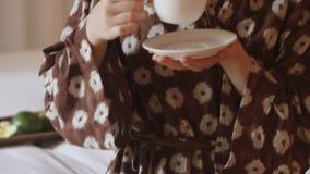 Gelukkige, mooie vrouw in badjas het drinken koffie stock videobeelden