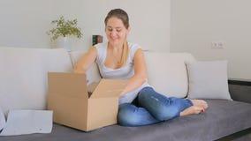 Gelukkige mooie vrouw die kleding nemen die zij online tot uit de doos opdracht heeft gegeven stock videobeelden