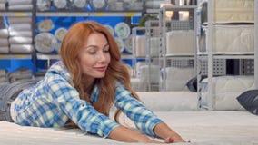 Gelukkige mooie vrouw die op een nieuwe orthopedische matras bij meubilairopslag liggen stock video