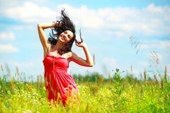 Gelukkige mooie vrouw die in weide danst Stock Foto