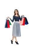 Gelukkige mooie vrouw met vele die het winkelen zakken op wit wordt geïsoleerd Stock Foto's