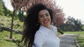 Gelukkige mooie vrouwengang in bloeiend park, langzame motie stock videobeelden