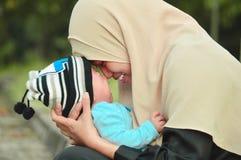 Gelukkige moslim hijab baart het houden van een mooie baby terwijl haar todler die in het openluchtgebied schreeuwen stock foto's