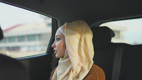 Gelukkige moslimvrouw in een auto op een passagiers achterzetel stock footage