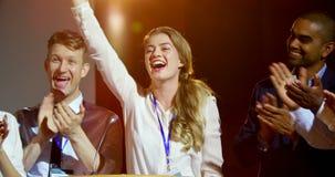 Gelukkige multi-etnische bedrijfsmensen die jonge onderneemster op stadium in seminarie 4k toejuichen stock footage