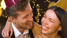 Gelukkige multi-etnische paar het vieren verjaardag, blazende partijventilator en het lachen stock video