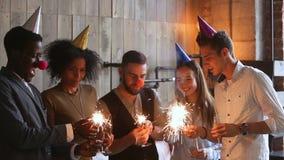 Gelukkige multi-etnische vrienden die fonkelingen aansteken die samen in partijhoeden vieren stock video