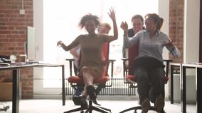 Gelukkige multiculturele beambten die hebbend pret die op stoelen berijden lachen stock videobeelden
