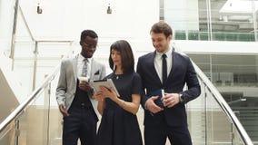 Gelukkige multiraciale bedrijfsmensen die neer op treden samen met digitale tablet lopen stock video