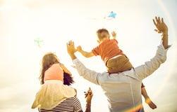 Gelukkige multiraciale familiesgroep met ouders en kinderen die met vlieger bij strandvakantie spelen - het concept van de de Zom royalty-vrije stock afbeelding