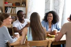 Gelukkige multiraciale vrienden die bij grap, het drinken koffie in koffie lachen stock foto's