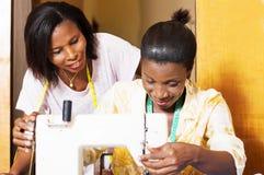 Gelukkige naaisters achter een naaimachine stock afbeelding