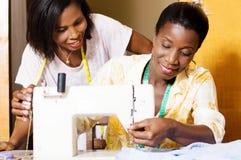 Gelukkige naaisters achter een naaimachine royalty-vrije stock afbeeldingen