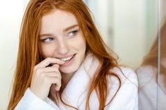 Gelukkige nadenkende roodharigevrouw in badjas Royalty-vrije Stock Foto