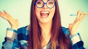 Gelukkige nerdy vrouw die in glazen pen houden Royalty-vrije Stock Fotografie