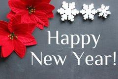 Gelukkige nieuwe jaar` s inschrijving Kerstmisbloem met rode bladeren van de poinsettia op een zwarte achtergrond stock fotografie
